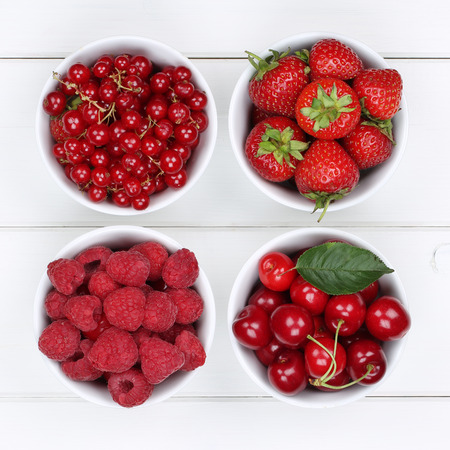 raspberries: Red berry fruits in bowls with strawberries, currants, cherries, raspberries Stock Photo
