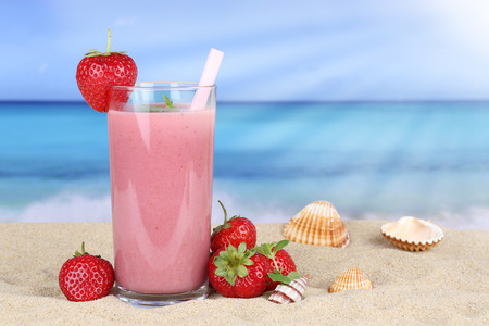 Strawberry smoothie fruit juice with strawberries fruits in summer on the beach