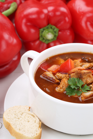 eating pastry: Goulash soup meal with meat, baguette and paprika in cup closeup