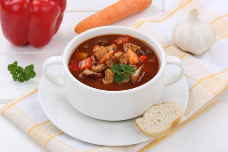 eating pastry: Goulash soup meal with meat, baguette and paprika in bowl Stock Photo