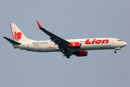 approaches: Singapore - October 21, 2015: A Lion Air Boeing 737-900ER with the registration PK-LGV approaches Singapore Airport (SIN). Lion Air is a low-cost airline from Indonesia based at Jakarta airport.