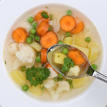 vegetable soup: Healthy eating vegetable soup meal with vegetables, potatoes, carrots and peas on spoon from above Stock Photo