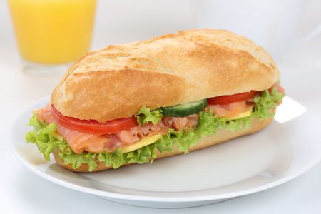 Sub deli sandwich baguette for breakfast with salmon fish, cheese, tomatoes, lettuce and orange juice