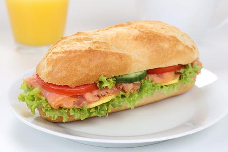 deli sandwich: Sub deli sandwich baguette for breakfast with salmon fish, cheese, tomatoes, lettuce and orange juice Stock Photo