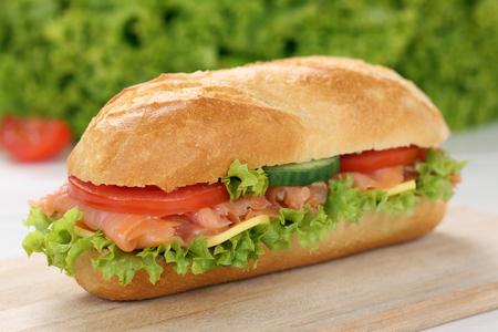 deli sandwich: Sub deli sandwich baguette with salmon fish, cheese, tomatoes and lettuce Stock Photo