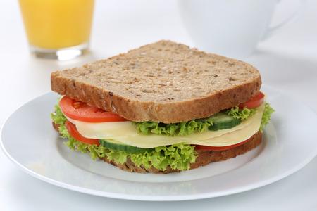 bocadillo: tostar el pan de sándwich para el desayuno con queso y zumo de naranja, el tomate, la lechuga Foto de archivo