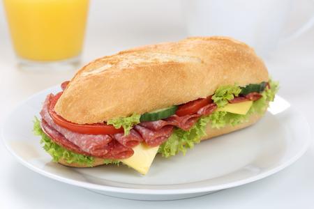 deli sandwich: Sub deli sandwich baguette for breakfast with salami ham, cheese, tomatoes, lettuce and orange juice