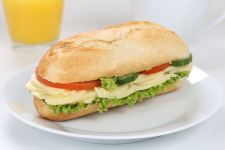 deli sandwich: Sub deli sandwich baguette for breakfast with cheese, tomatoes, lettuce and orange juice