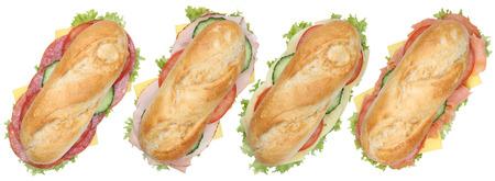 Colección de sub sándwiches baguettes deli en una fila con salami, jamón y vista superior queso aislado en un fondo blanco Foto de archivo