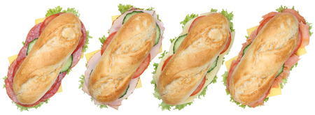 Collection of sub deli sandwiches baguettes in a row with salami, ham and cheese top view isolated on a white background Reklamní fotografie
