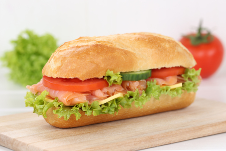 sub sandwich: Sub deli sandwich baguette with salmon fish, cheese, tomatoes and lettuce for breakfast