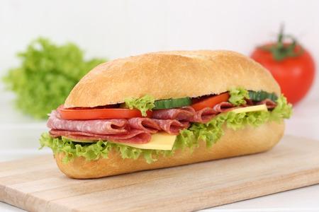 deli sandwich: Sub deli sandwich baguette with salami ham, cheese, tomatoes and lettuce for breakfast