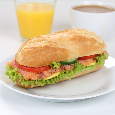 deli: Healthy eating sub deli sandwich baguette for breakfast with salmon fish, cheese, tomatoes, lettuce and orange juice