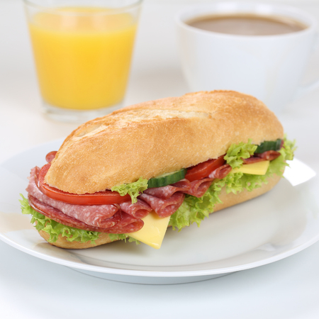 deli sandwich: Healthy eating sub deli sandwich baguette for breakfast with salami ham, cheese, tomatoes, lettuce and orange juice