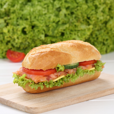 deli sandwich: Healthy eating sub deli sandwich baguette with salmon fish, cheese, tomatoes and lettuce