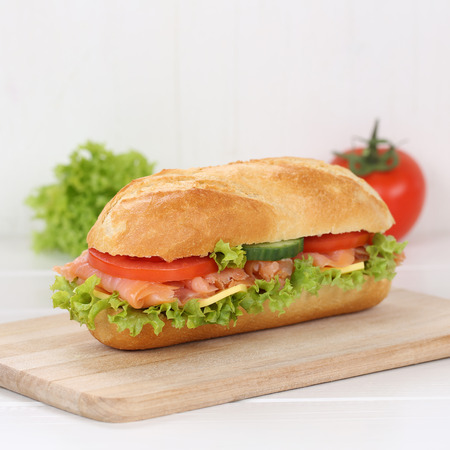 deli sandwich: Healthy eating sub deli sandwich baguette with salmon fish, cheese, tomatoes and lettuce for breakfast