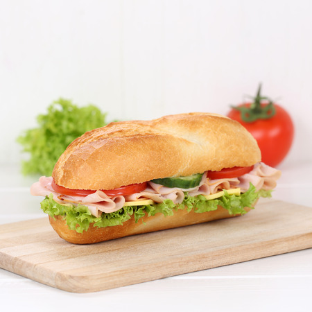 Healthy eating sub deli sandwich baguette with ham, cheese, tomatoes and lettuce for breakfast