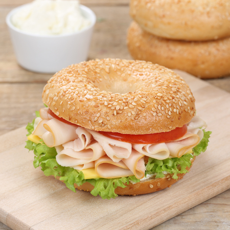 cream cheese: Healthy eating bagel sandwich for breakfast with ham, cream cheese, tomatoes and lettuce