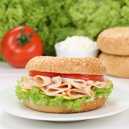 Healthy eating bagel for breakfast with ham, cream cheese, tomatoes and lettuce