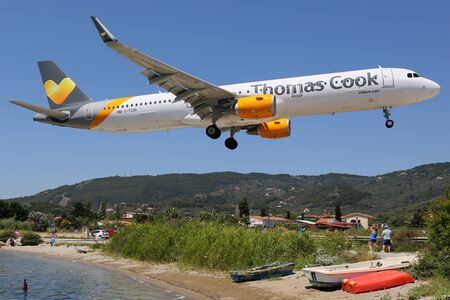 skiathos: Skiathos, Greece - June 24, 2015: A Thomas Cook Airlines Airbus A321 with the registration G-TCDK approaching Skiathos Airport (JSI). Thomas Cook Airlines is a British airline based in Manchester. Skiathos ranks as one of the most dangerous airports in th