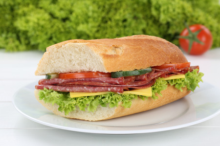 sub sandwich: Sub sandwich baguette on plate with salami ham, cheese, tomatoes and lettuce for breakfast Stock Photo