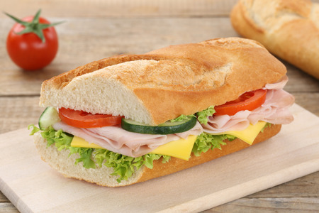 sub sandwich: Sub sandwich baguette with ham, cheese, tomatoes and lettuce for breakfast