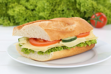 eating pastry: Sub sandwich baguette on plate with cheese, tomatoes and lettuce for breakfast Stock Photo