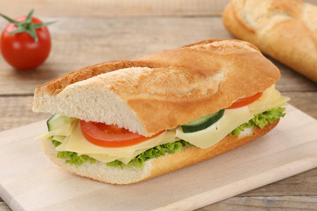 eating pastry: Sub sandwich baguette with cheese, tomatoes and lettuce for breakfast