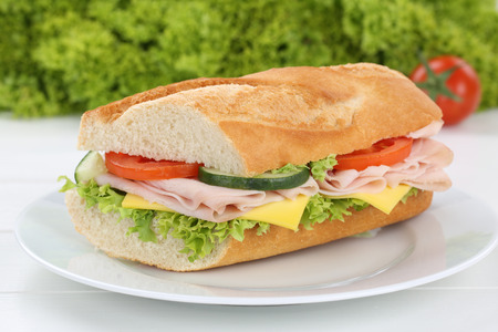 sub sandwich: Sub sandwich baguette on plate with ham, cheese, tomatoes and lettuce for breakfast