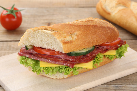 Sub sandwich baguette with salami ham, cheese, tomatoes and lettuce for breakfast