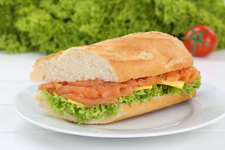 sub sandwich: Sub sandwich baguette on plate with salmon fish, cheese, tomatoes and lettuce for breakfast Stock Photo