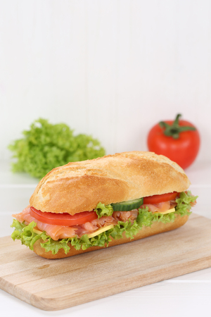 deli: Sub deli sandwich baguette with salmon fish, cheese, tomatoes and lettuce  copy space Stock Photo