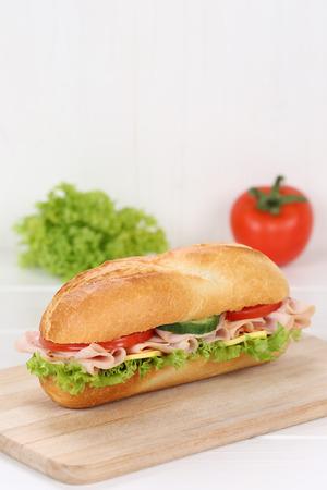 deli sandwich: Sub deli sandwich baguette with ham, cheese, tomatoes and lettuce  copy space