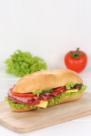 deli sandwich: Sub deli sandwich baguette with salami, cheese, tomatoes and lettuce  copy space