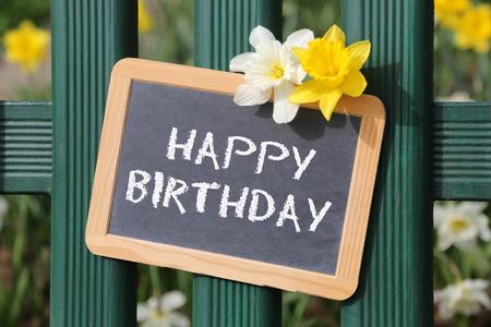 flores de cumpleaños: Tarjeta del jardín feliz cumpleaños con las flores de la flor tarjeta de la muestra en la cerca Foto de archivo