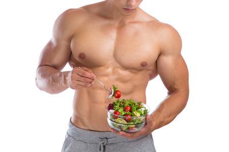 fitness hombres: comer alimentos ensalada culturismo culturista culturista construcción de los músculos sanos hombre joven muscular aislado en un fondo blanco