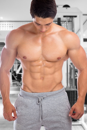 sixpack: Bodybuilder bodybuilding muscles abs sixpack fitness gym strong muscular man looking down studio Stock Photo