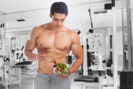 man gym: Eating food salad bodybuilding bodybuilder fitness gym body builder building muscles young man studio