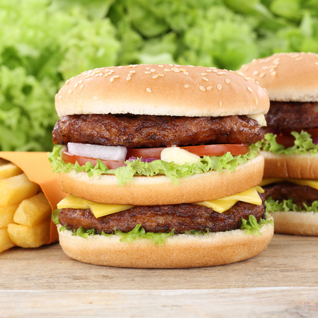 eating pastry: Double burger hamburger and fries tomatoes lettuce fast food