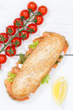 Sub sandwich whole grain grains baguette with salmon fish portrait format from above on wooden board wood Stock Photo