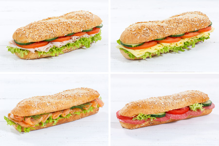 Collection of baguette sub sandwiches with salami ham cheese salmon fish whole grains fresh on a wooden board wood