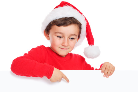 Boy wearing santa hat pointing at empty banner with copyspace
