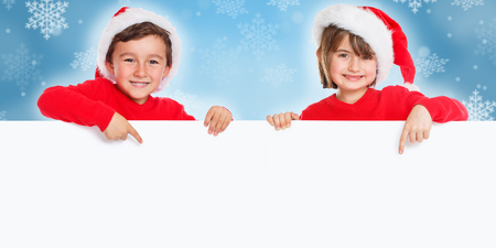 Children wearing Santa hat pointing happy empty banner copyspace copy space Stock Photo