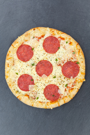 Pizza salami portrait format from above on a slate