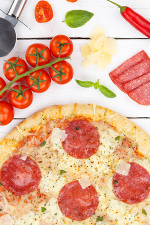 Pizza salami from above baking ingredients portrait format close up on wooden board wood