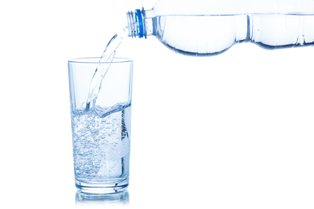 Water pouring into glass bottle isolated on a white background