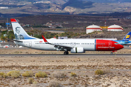 Tenerife, Spain - November 23, 2019: Norwegian Boeing 737-800 airplane at Tenerife South Airport in Spain. Boeing is an American aircraft manufacturer headquartered in Chicago. 新闻类图片