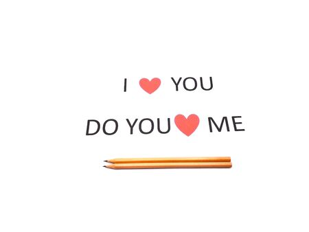 Note I LOVE YOU sentence words written on white paper with two brown wood pencils.