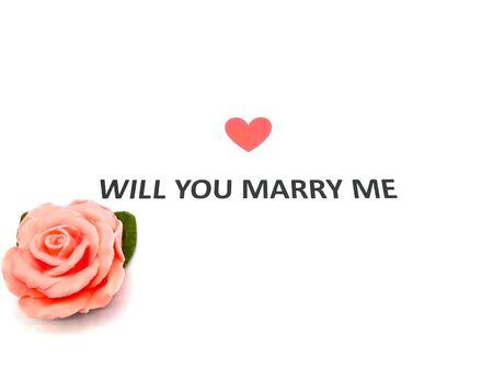 Beachten Sie, werden Sie mich heiraten Satzwörter auf weißem Papier mit roter Rose geschrieben.