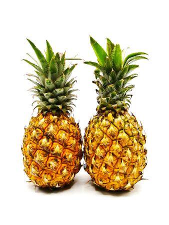 Two whole ripe pineapple fruit isolated on white background